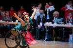 female Para dancer in a wheelchair throwing her arms out and smiling