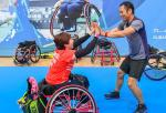 female Para badminton player Yuma Yamazaki sits in a wheelchair and high fives a standing man