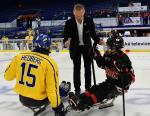 male able-bodied ice hockey player Dominik Hasek drops the puck on the ice ahead of a Para ice hockey match