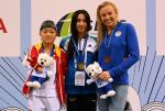 three female swimmers on the podium holding their medals and mascot teddys