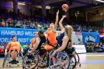female wheelchair basketball players from Netherlands and Great Britain reaching up for the ball