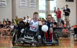Two male wheelchair rugby players collide trying to fight for a loose ball