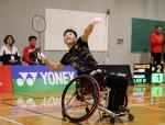 Korean male badminton player in wheelchair leans back to hit a birdie