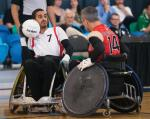 Swiss man in wheelchair rugby protects the ball against his opponent