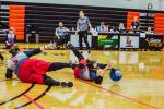 A female goalballer slides to block the ball from entering the goal
