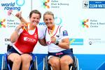 two female Para rowers in wheelchairs side hug on the podium