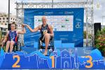 female Para triathlete Christiane Reppe holds the hand of another female athlete on the podium