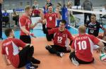 Russian men's sitting volleyball players celebrate on the court after scoring a point