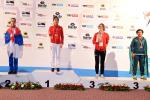 four female taekowondo fighters on the podium with Yujie Li on the top step