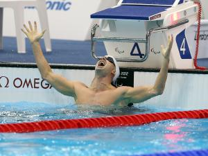 A picture of a man with his hands up in the pool