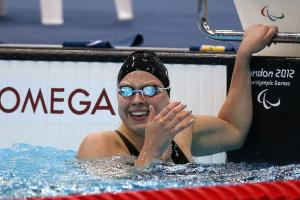 A picture of a woman in the pool holding the starting block with her hand