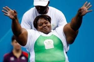 A picture of a woman powerlifter on a bench celebrating with her hands up