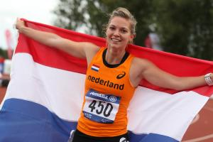 Women with a Dutch flag smiles to the camera