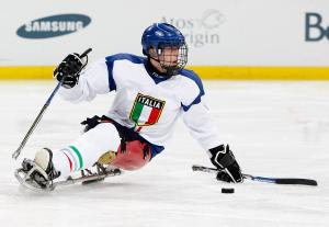 A picture of a man in a sledge practising Ice Sledge Hockey.