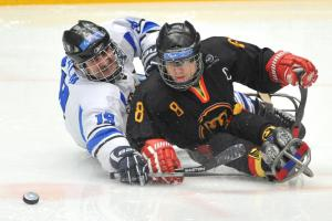 A picture of two men in sledge fighting the puck during a ice hockey match