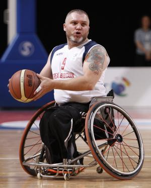 A picture of an athlete with a wheelchair playing basketball