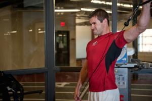 An athlete works out his shoulders in the gym.