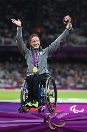 A picture of a woman on a podium with the medal around her neck and with her hands up