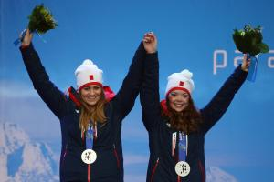Two young women wearing ski clothes and a silver medal holding hands and waving