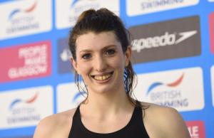 A swimmer smiles having won gold and set a new world record