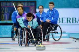 Woman throwing a stone in wheelchair curling.