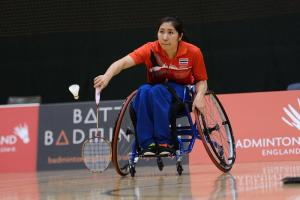 Women in wheelchair playing badminton on the court.