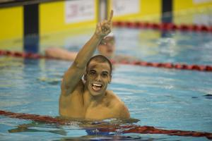 Man in water, holding one arm in the air, celebrating