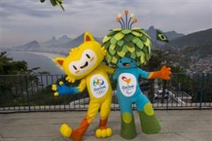 A yellow mascots and blue mascot with green leaves as hair stand on top of Rio's Sugar Loaf mountain.
