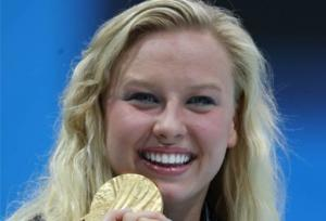 A portrait of a blond woman showing her gold medal