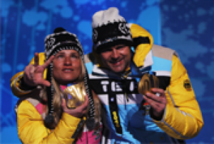 A picture of a woman showing her gold medal with a man during a medal ceremony