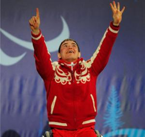 A picture of a man in a wheelchair celebrating his victory during a medal ceremony