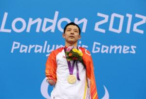 A picture of a man standing with his gold medal around his neck during a medal ceremony