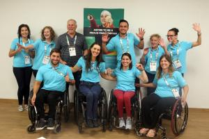 a group of para athletes raise their arms for a photo