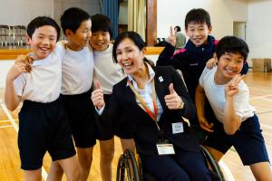 A group of children pose with a wheelchair athlete