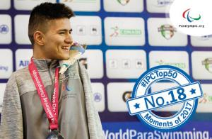 a male Para swimmer smiles on the podium with his medal
