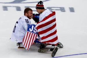 two male Para ice hockey players embrace on the ice