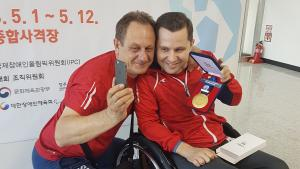 a male Para shooter and his coach hold up his gold medal