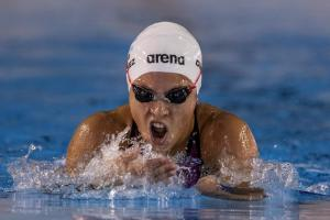 a female Para swimmer comes out of the water to take a breath