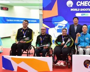 Three shooters in wheelchairs pose on the podium