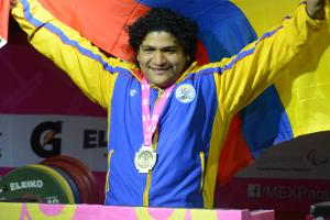 a male powerlifter smiling with his medal round his neck holding up a Colombian flag