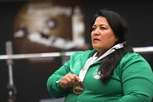 Woman wearing a green jacket holding a gold medal