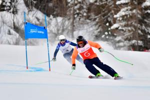 Female Para alpine skier Kelly Gallagher skis round a gate following her guide