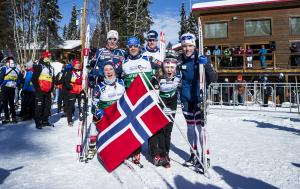 Group of Norwegian cross-country skiers happy posing together after a win