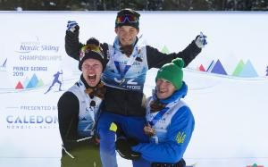 male Para Nordic skier Taiki Kawayoke is held in the air by two other skiers as he raises his arms in celebration