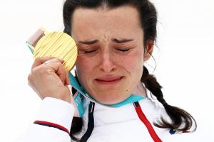 female Para alpine skier Marie Bochet holds her gold medal up to her face