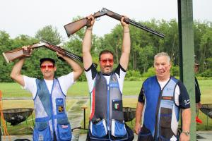 Three male Para trap shooters pose together with man in middle raising his shot gun over his head