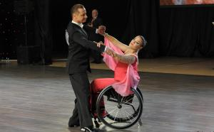 Male standing dancer dances with female partner in wheelchair