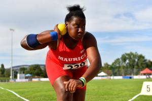 A young woman competing in shot put